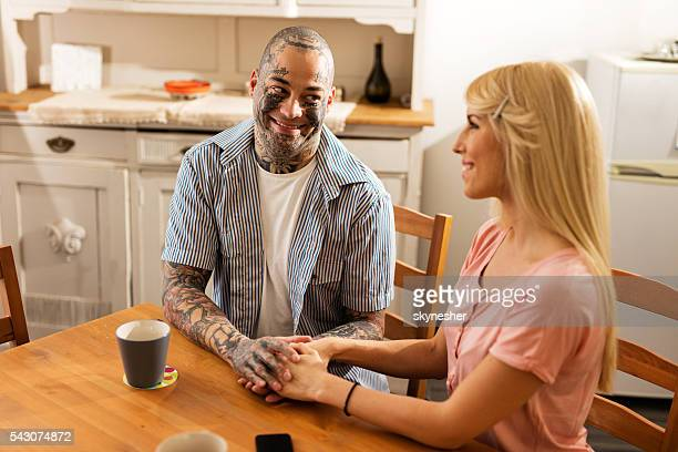 Smiling man holding hands with his girlfriend in the kitchen.