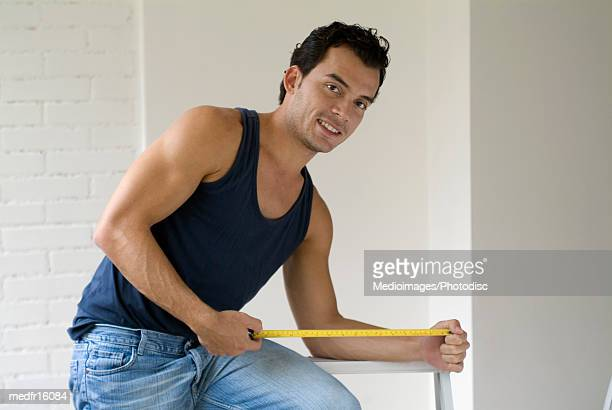 smiling man holding measuring tape - meter unit of length stock pictures, royalty-free photos & images