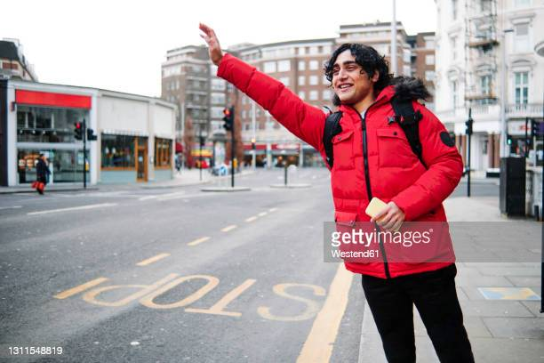 smiling man holding mobile phone while hailing ride on footpath - western script stock pictures, royalty-free photos & images