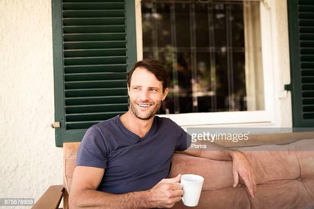 Smiling man holding mug while sitting on sofa