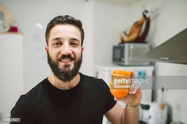 Smiling man holding orange peels