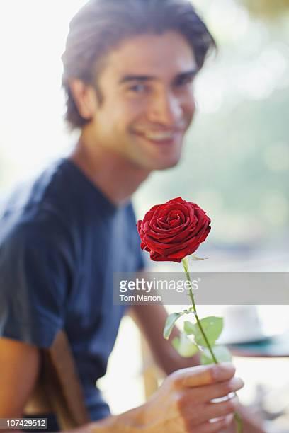 Lächelnder Mann hält eine rote rose