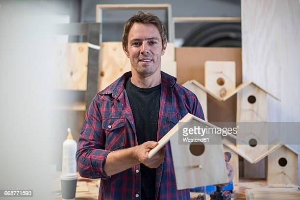 Smiling man holding self-made birdhouse in workshop