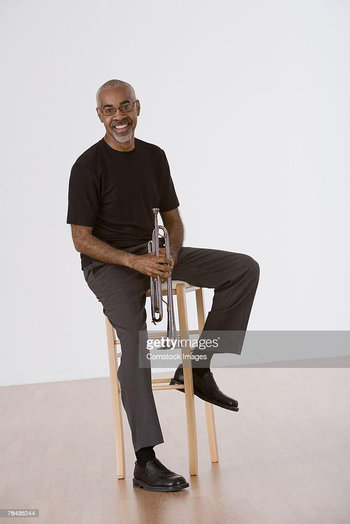 Smiling man holding trumpet : Stockfoto