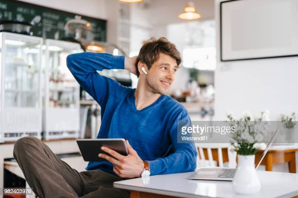 smiling man in a cafe with earphone, laptop and tablet - wireless technology stock pictures, royalty-free photos & images