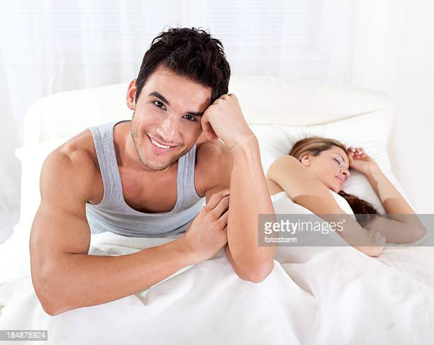 Smiling man in bed with beautiful sleepy woman