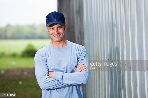 Smiling man in cap standing  outside building