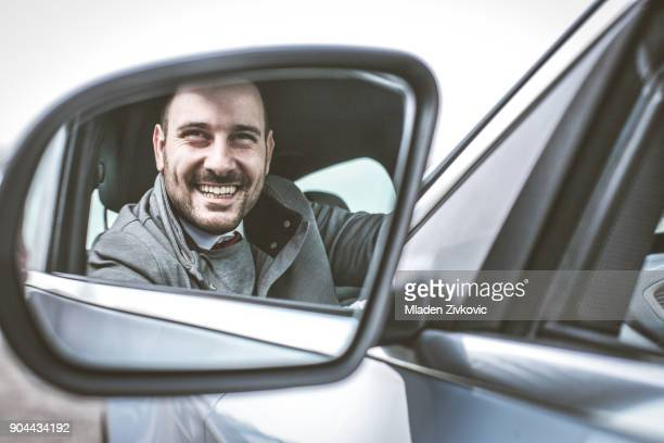 smiling man in car. - rear view mirror stock pictures, royalty-free photos & images