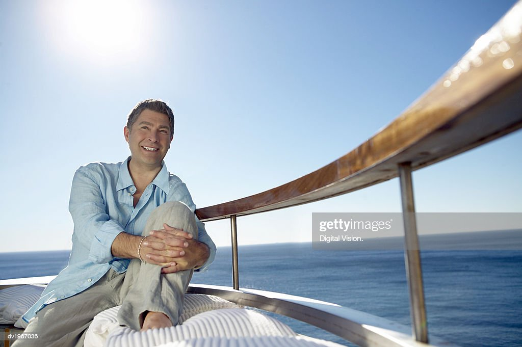 Smiling Man in Casual Summer Clothing Sits on a Sunlit Balcony by the Sea : Stock Photo