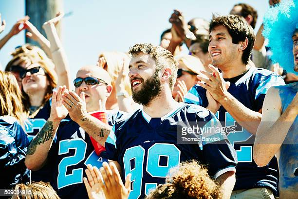 smiling man in crowd of celebrating football fans - match sport stock pictures, royalty-free photos & images