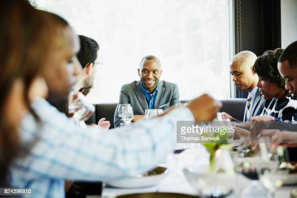 Smiling man in discussion with family and friends during celebration meal in restaurant