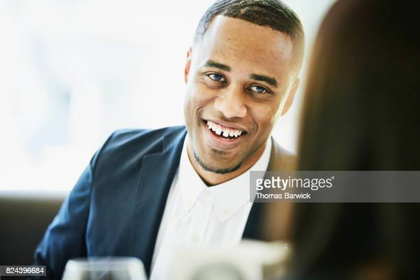 Smiling man in discussion with friend during meal in restaurant