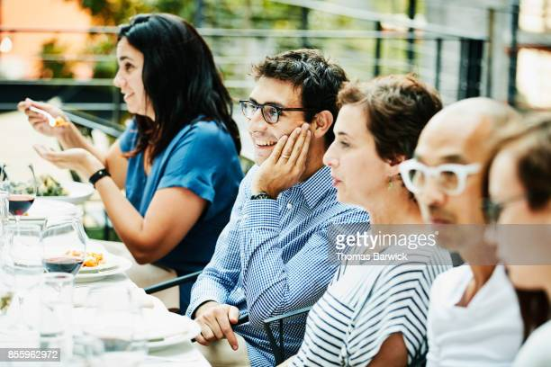 Smiling man in discussion with friends during celebration dinner on outdoor patio