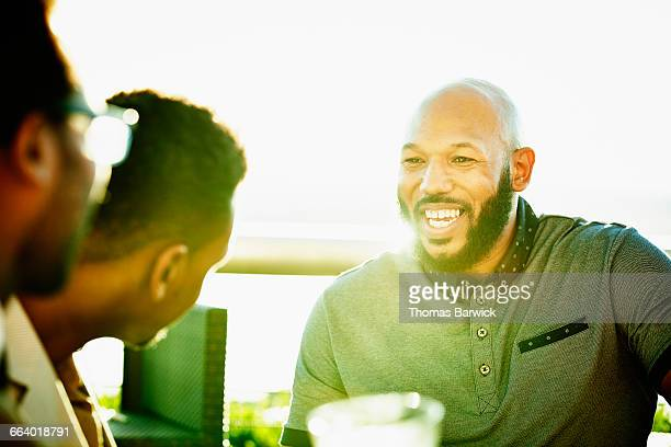 smiling man in discussion with friends on deck - only mid adult men stock pictures, royalty-free photos & images