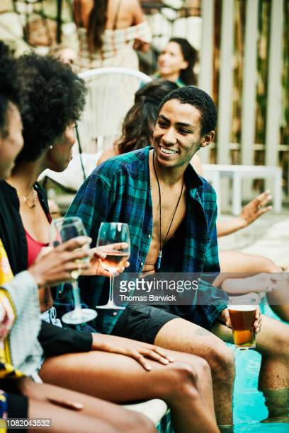 smiling man in discussion with friends while sitting by hotel pool during party - poolside stock pictures, royalty-free photos & images