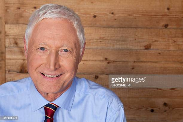 Smiling man in front of wooden wall