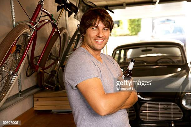 Smiling man in garage with bottle of beer and vintage car