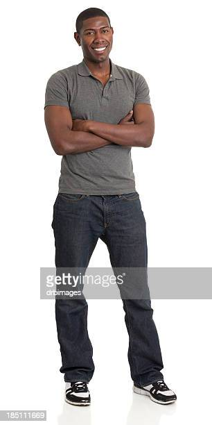 Smiling man in gray shirt and blue jeans with arms crossed