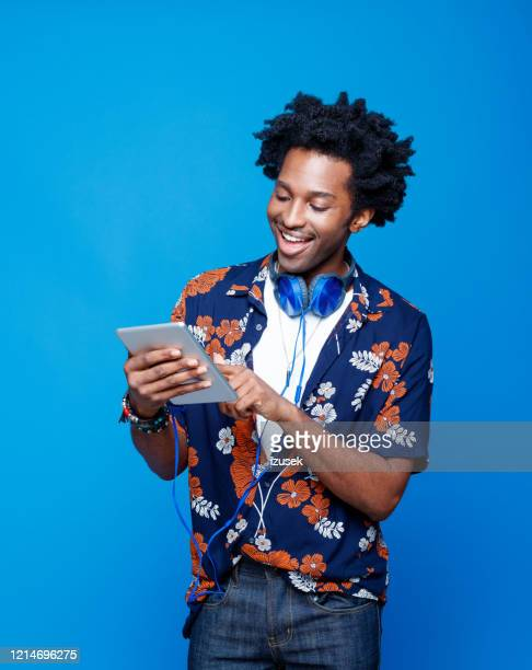 smiling man in hawaiian shirt holding digital tablet - portable information device stock pictures, royalty-free photos & images