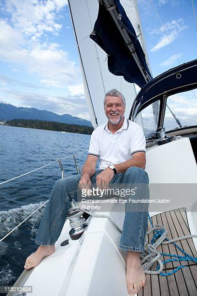 """smiling man in jeans sitting on a sailboat - """"compassionate eye"""" stock pictures, royalty-free photos & images"""