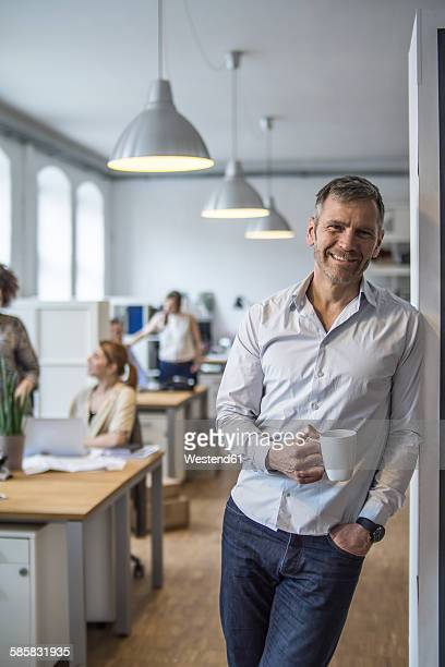 Smiling man in office with colleagues in background