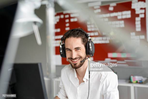 Smiling man in office with headset