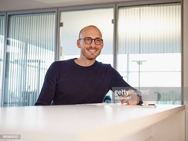 Smiling man in office writing at counter