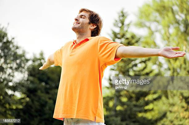 Smiling man in orange shirt with arms wide open outdoors