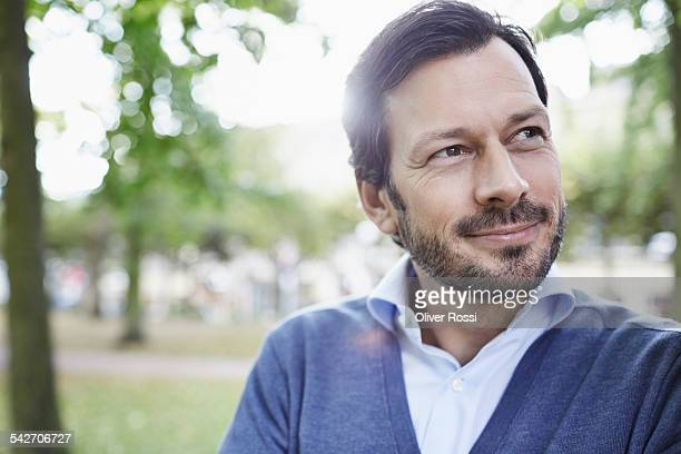 Smiling man in park contemplating