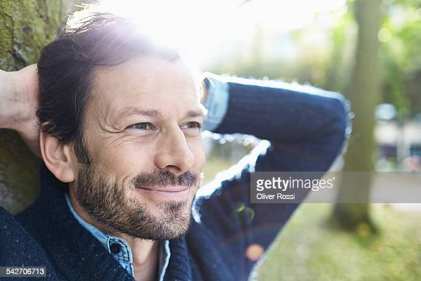 smiling man in park - satisfaction stock pictures, royalty-free photos & images