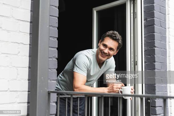 smiling man in pyjama at home with cup of coffee looking out of balcony door - garde corps photos et images de collection
