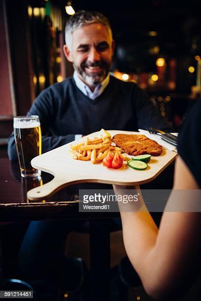 Smiling man in restaurant receiving Wiener Schnitzel with French fries
