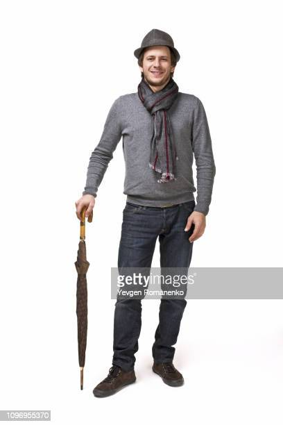 smiling man in scarf and hat, standing on white background with umbrella - white jacket stock pictures, royalty-free photos & images