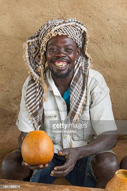 Smiling Man in scarf drinking homemade Sorghum Tella from Calabash in Southern Ethiopia.
