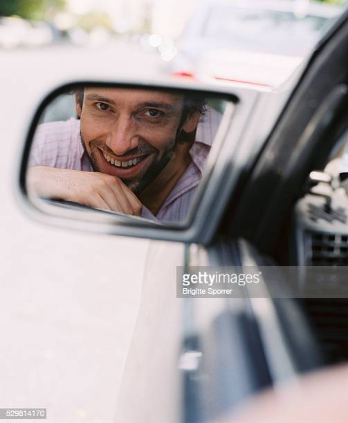 Smiling Man in Side Mirror of Car