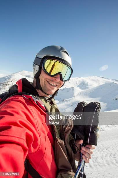 Smiling man in ski-wear standing on snow covered field against clear sky