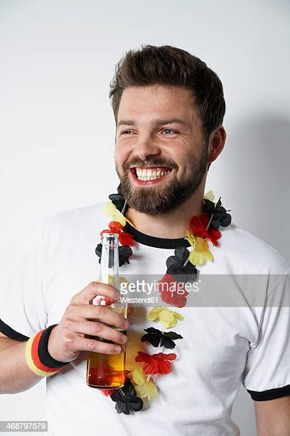 smiling man in soccer jersey holding beer bottle - sports jersey stock pictures, royalty-free photos & images