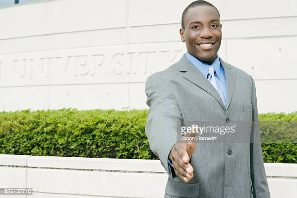 Smiling Man in Suit Standing in Front of 'University' Sign