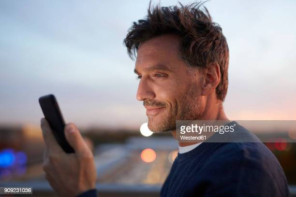 smiling man in the city checking cell phone in the evening - sehen stock-fotos und bilder