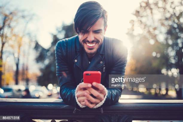 Smiling man in the city text messaging