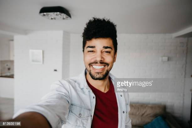 Smiling man in the living room is taking a selfie