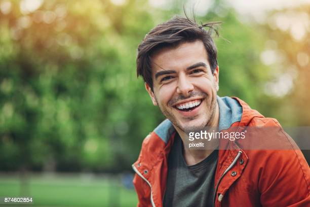 smiling man in the park - toothy smile stock pictures, royalty-free photos & images
