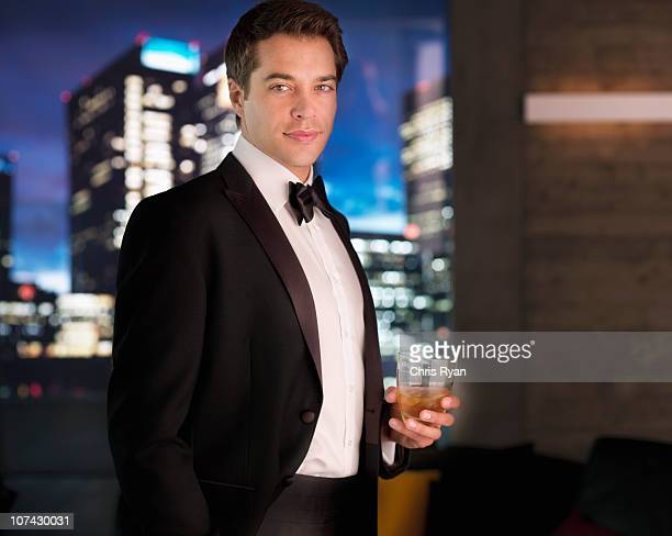smiling man in tuxedo drinking cocktail - dinner jacket stock pictures, royalty-free photos & images
