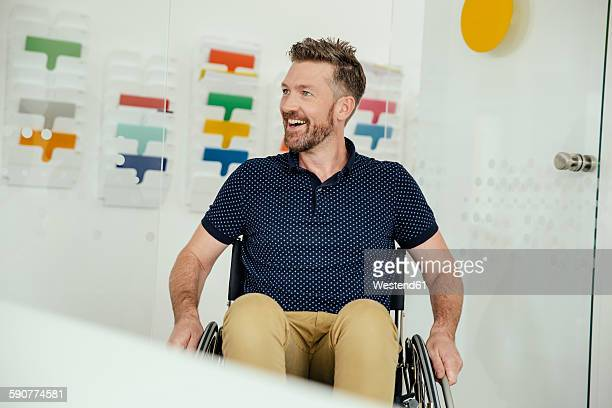 Smiling man in wheelchair in modern office