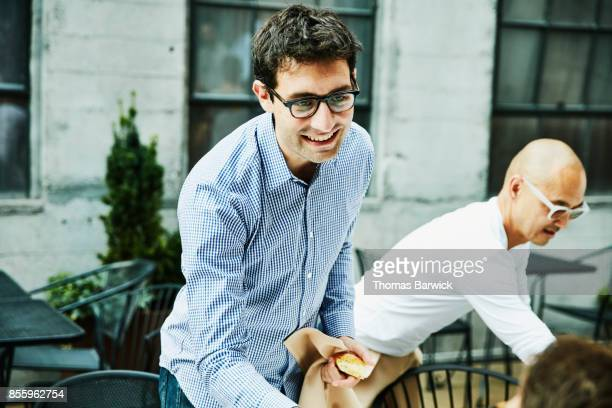 Smiling man introducing himself while being seated for celebration dinner on restaurant patio