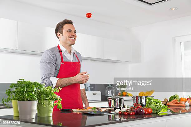 Smiling man juggling with tomatoes in kitchen