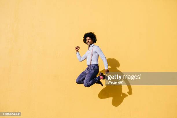 smiling man jumping in the air in front of yellow wall - jumping stock pictures, royalty-free photos & images