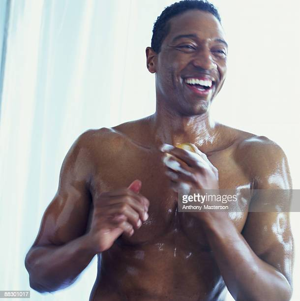 Smiling man lathering with soap