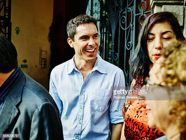 smiling man laughing with family during party - black hair stock pictures, royalty-free photos & images