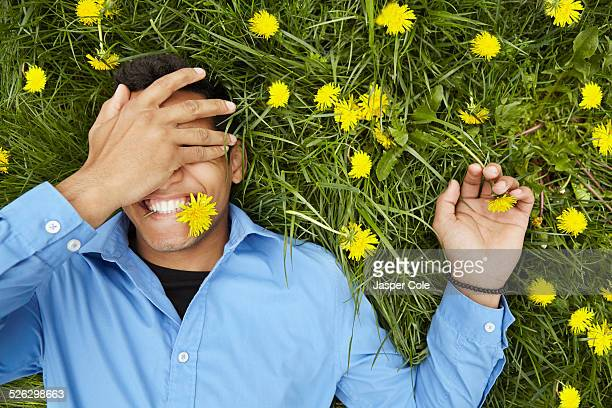Smiling man laying in field of flowers
